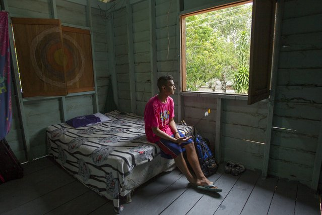 Kambeba Indian, Dream Braga, 18, looks out from his window at his home in the village Tres Unidos, Amazon state May 10, 2015. (Photo by Bruno Kelly/Reuters)