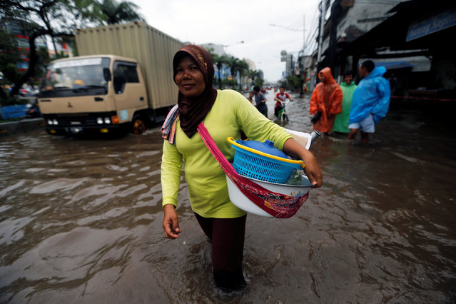 A street vendor wades through floodwaters in a flood-hit area at the Mangga Dua business district in Jakarta, Indonesia February 21, 2017. (Photo by Reuters/Beawiharta)