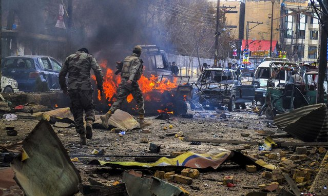 Pakistani paramilitary soldiers run through the bombing site where nearly a dozen people were killed when a bomb went off near a passenger bus in Quetta, on March 14, 2014. (Photo by Arshad Butt/Associated Press)