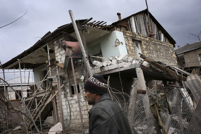 An ethnic Armenian man walks past a destroyed house during the fighting in Martakert province in the separatist region of Nagorno-Karabakh, Azerbaijan, Monday, April 4, 2016. (Photo by Vahan Stepanyan/PAN Photo via AP Photo)