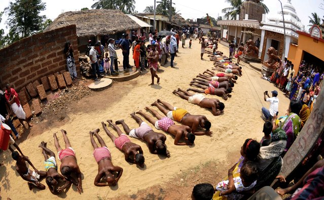 Indian devotees roll on sand as as they offer prayers to the Hindu God Shiva during a ritual as part of The Danda Festival which coincides with The Oriya New Year in the village of Mendhasala Village, on the outskirts of Bhubaneswar on April 12, 2016. Devotees inflict physical pain on themselves as they perform rituals of penance to appease Shiva, the Hindu God of destruction during the Danda festival, or the festival of self-punishment. (Photo by Asit Kumar/AFP Photo)