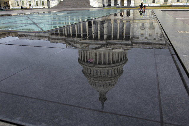 The U.S. Capitol is seen reflected after rain in Washington, Friday, December 21, 2018. The Republican-led House approved funding for President Donald Trump's border wall in legislation that pushes the government closer to a partial government shutdown. The bill now goes to the Senate. (Photo by Jose Luis Magana/AP Photo)