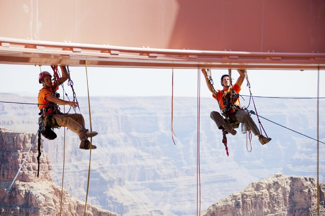 Technicians from Abseilon USA work to clean more than 40 panes of glass underneath the horseshoe-shaped bridge at the Grand Canyon Skywalk in Arizona in this handout picture courtesy of George & Pat Walsh of GPWalshPhotography.com, taken March 24, 2014. (Photo by George & Pat Walsh/Reuters)