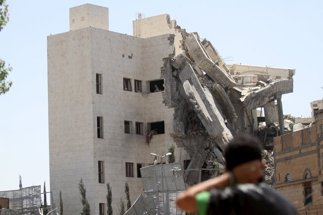 A man looks toward the residence of the Yemen's former President Ali Abdullah Saleh after airstrikes destroyed it in Sanaa May 10, 2015. (Photo by Mohamed al-Sayaghi/Reuters)