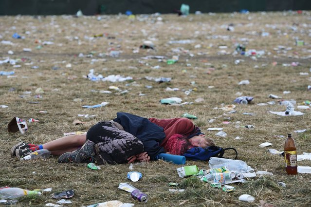 A couple sleep on the ground in front of the pyramid stage at Glastonbury Festival of Music and Performing Arts on Worthy Farm near the village of Pilton in Somerset, South West England, on July 1, 2019. (Photo by Oli Scarff/AFP Photo)