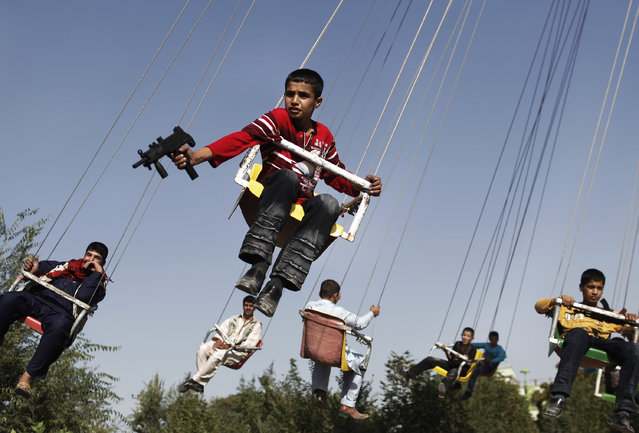 In this Sunday, September 20, 2009 file photo, an Afghan boy holds a toy gun as he enjoys a ride with others on a merry-go-round to celebrate the Eid al-Fitr festival, in Kabul, Afghanistan. (Photo by Anja Niedringhaus/AP Photo)