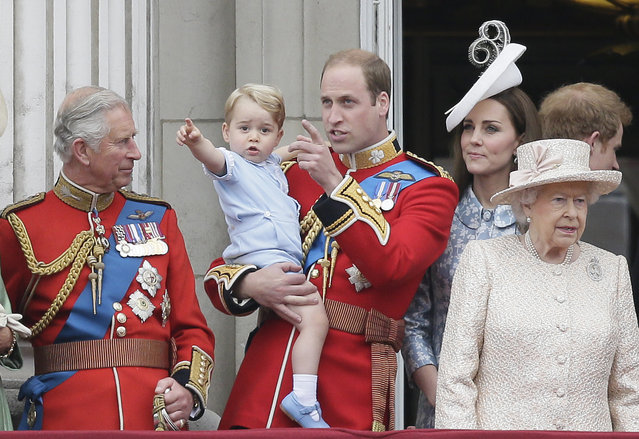 """Britain's Prince William holds his son Prince George, with Queen Elizabeth II, right, Kate, Duchess of Cambridge and the Prince of Wales during the Trooping The Colour parade at Buckingham Palace, in London, Saturday, June 13, 2015. Hundreds of soldiers in ceremonial dress have marched in London in the annual Trooping the Color parade to mark the official birthday of Queen Elizabeth II. The Trooping the Color tradition originates from preparations for battle, when flags were carried or """"trooped"""" down the rank for soldiers to see. (AP Photo/Tim Ireland)"""