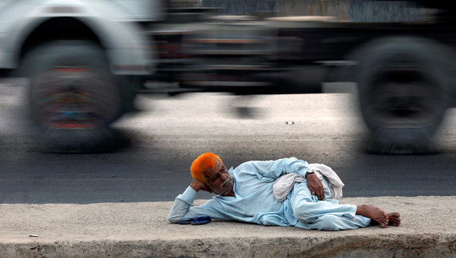 A man with henna-dyed hair rests on a road near the port area in Karachi, Pakistan on July 3, 2019. (Photo by Akhtar Soomro/Reuters)