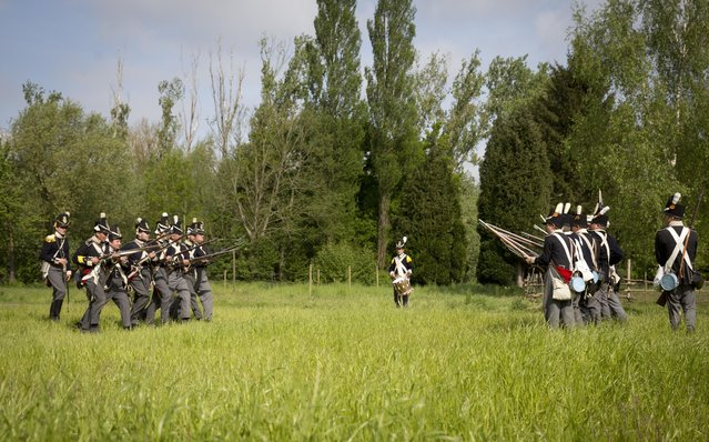In this May 10, 2015, photo, historical re-enactors dressed as soldiers of the Belgian-Dutch 7th Battalion of the Line face off against each other in a mock battle at a Napoleonic era living history camp in Elewijt, Belgium. The Belgian-Dutch living history group is coordinating their group for participation in the 200th anniversary of the Battle of Waterloo which will take place in June 2015. (AP Photo/Virginia Mayo)