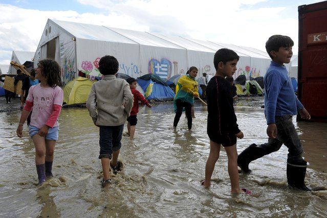 Children play in a puddle following heavy rainfall at a makeshift camp for migrants and refugees at the Greek-Macedonian border near the village of Idomeni, Greece, April 24, 2016. (Photo by Alexandros Avramidis/Reuters)