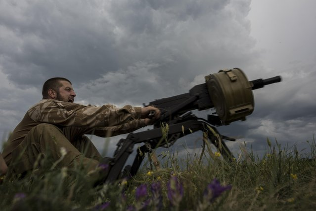 In this photo taken Tuesday, June 23, 2015, a Ukrainian serviceman from the Kiev-2 volunteer battalion fires an weapon at a frontline in the village of Krymske, east Ukraine. (Photo by Evgeniy Maloletka/AP Photo)