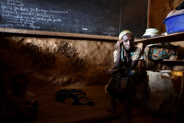 An internally displaced Congolese woman and her child sit inside a classroom used by victims of ethnic violence in Iga Barriere, Ituri province, in the eastern Democratic Republic of Congo on June 24, 2019. (Photo by Olivia Acland/Reuters)
