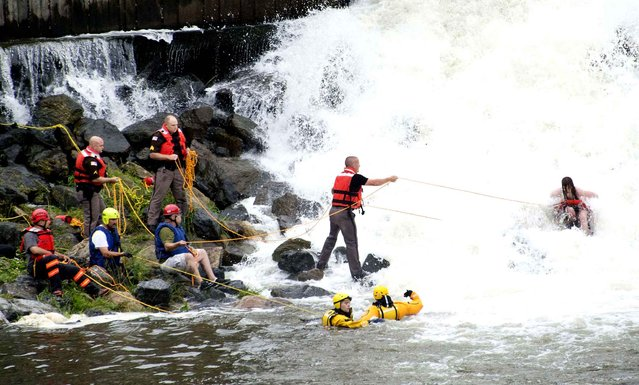 In this Saturday, June 27, 2015 photo, one of the teenagers who was swept over the spillway at the Lake Linganore dam has a line thrown to her by nearby rescuers near New Market, Md. Eight people were rescued from the water and there was 1 fatality. An autopsy has concluded the operator of a pontoon boat that went over a dam near New Market died from accidental drowning, Monday, June 29, 2015. (Photo by Sam Yu/The Frederick News-Post via AP Photo)