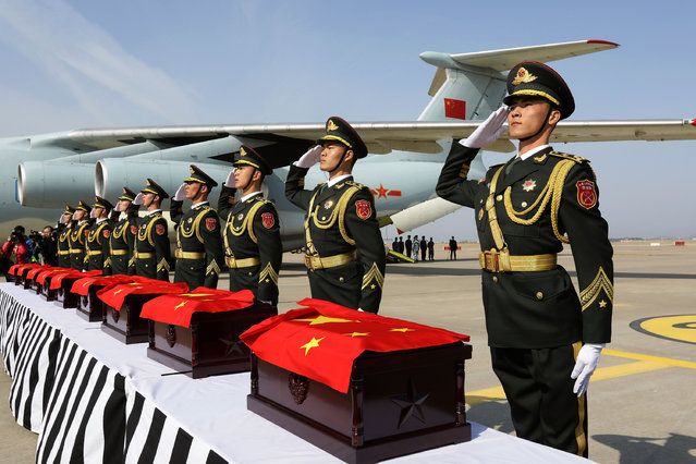 Chinese soldiers salute after carry coffins containing the remains remains of Chinese military personnel who died during the 1950-53 Korean War to the Chinese side at Incheon International Airport on March 22, 2017 in Incheon, South Korea. (Photo by Chung Sung-Jun/Getty Images)