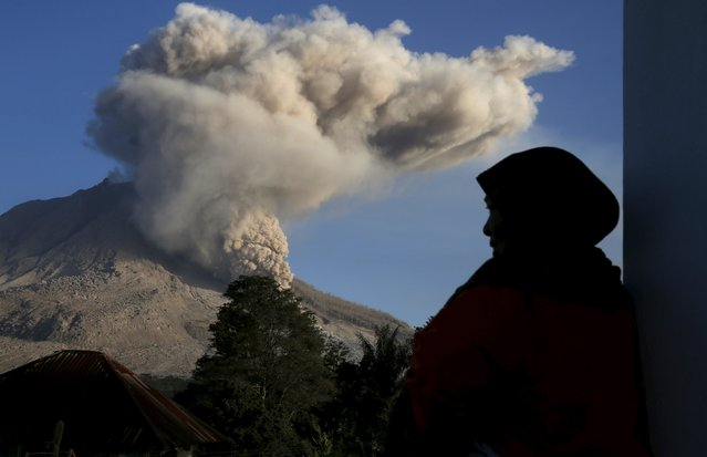 A woman looks as ash spews from Mount Sinabung volcano during  an eruption at Kuta Tengah village in Karo Regency, North Sumatra province, Indonesia June 30, 2015. (Photo by Reuters/Beawiharta)