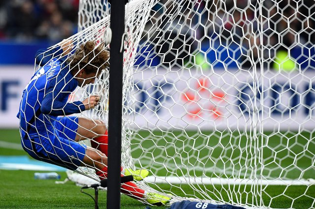 France's forward Antoine Griezmann falls into the net of the goal during the friendly football match France vs Spain on March 28, 2017 at the Stade de France stadium in Saint-Denis, north of Paris. Spain won the match 0–2. (Photo by Franck Fife/AFP Photo)