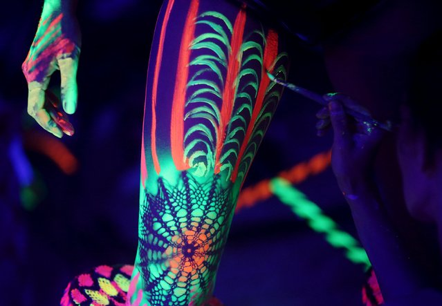 An artist paints a model under ultraviolet light paint during the annual World Bodypainting Festival in Poertschach, Austria, July 3, 2015. (Photo by Heinz-Peter Bader/Reuters)