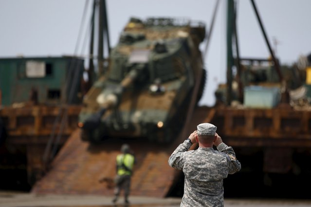 A U.S. Marine takes photographs of a South Korean army's K-55 self-propelled artillery vehicle getting out of a barge during the Combined Joint Logistics Over The Shore (CJLOTS) exercise, at a seashore in Taean, South Korea, July 6, 2015. (Photo by Kim Hong-Ji/Reuters)