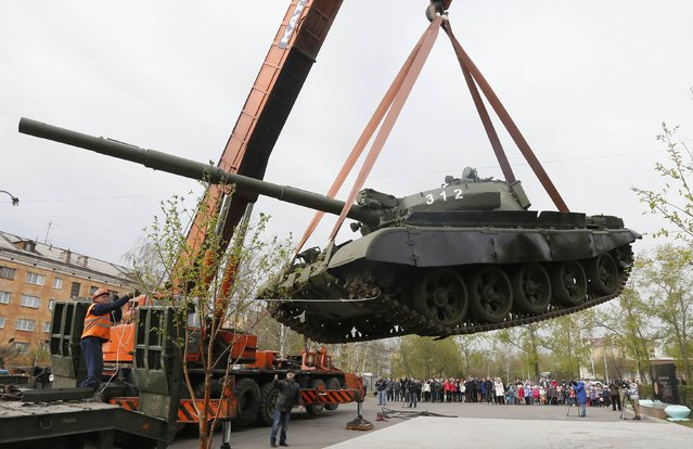 Workers install a demilitarized Soviet-made T-62M1 tank at a memorial in a park in Russia's Siberian city of Krasnoyarsk April 30, 2014. (Photo by Ilya Naymushin/Reuters)