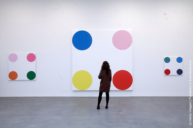An employee looks at the artwork 4-Chlorephenol, 2008, part of the artist Damien Hirst's exhibition The Complete Spot Paintings