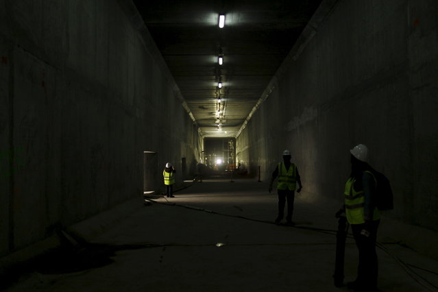 Workers and members of the media are seen inside a tunnel at the Panama Canal expansion project site in Panama City March 26, 2015. (Photo by Carlos Jasso/Reuters)