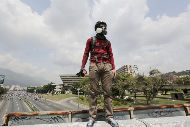 A demonstrator stands atop an overpass during anti-government protests in Caracas, Venezuela, Wednesday, April 19, 2017. (Photo by Fernando Llano/AP Photo)