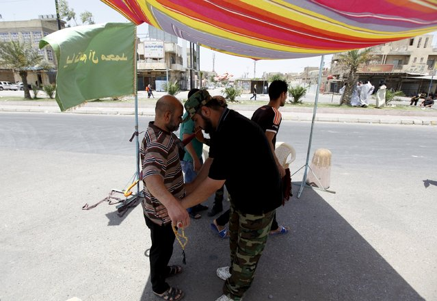 A member of Hashid Shaabi (Popular Mobilization) checks Muslims who are attending Friday prayers in Baghdad's Sadr City July 10, 2015. (Photo by Ahmed Saad/Reuters)