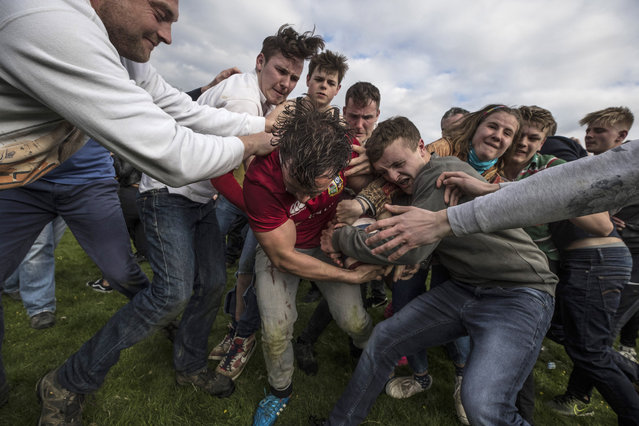 """The second round of the bottle Kicking gets underway over the Hare Pie Hill on April 17, 2017 in Hallaton, England. Hallaton hosts the Hare Pie Scramble and Bottle Kicking event today. The Bottle Kicking follows the Hare Pie Scramble, two events that are combined to form an ancient custom that dates back to the early eighteenth century, and one of the oldest in British History. The first part consists of a blessing of a Hare Pie by a local vicar, before it is cut up and thrown to the crowd, who 'scramble' to get a piece, believing it will bring good luck. The second part, the Bottle kicking sees two rival villages, Hallaton, and neighboring Medbourne attempt to carry a """"bottle"""" which is actually a keg of beer, from the Hare Pie Bank, and get it across a boundary stream for their own village. The best of three contest can last several hours. (Photo by Dan Kitwood/Getty Images)"""
