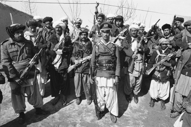 A mujahedeen, a captain in the Afghan army before deserting, poses with a group of rebels near Herat, Afghanistan, February 28, 1980.  It was reported that the Afghan capital of Kabul returned to normal for the first time since bloody anti-Soviet rioting erupted there last week, killing more than 300 civilians and an unknown number of Soviet and Afghan soldiers. (Photo by Jacques Langevin/AP Photo)