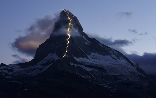Solar powered lights are pictured along the Hoernli ridge on the Matterhorn in Zermatt, Switzerland, July 13, 2015. Zermatt celebrates the first ascent of the Matterhorn on the Hoernli ridge made by Briton Edward Whymper on July 14, 1865, with 6 other roped team members. (Photo by Denis Balibouse/Reuters)