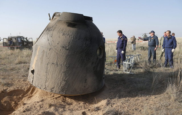 Rescue team members arrive as the Russian Soyuz TMA-11M space capsule rests on the ground shortly after landing south-east of the town Dzhezkazgan, Kazakhstan, May 14, 2014. A Soyuz space capsule with Japanese astronaut Koichi Wakata, Russian cosmonaut Mikhail Tyurin and U.S. astronaut Rick Mastracchio, returning from a five-month mission to the International Space Station, landed safely Wednesday on the steppes of Kazakhstan. (Photo by Dmitry Lovetsky/Reuters)