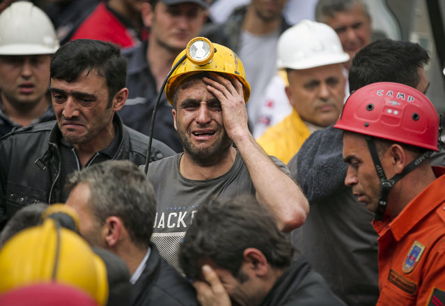 A miner cries as rescue workers carry the dead body of a miner from the mine in Soma, western Turkey, Wednesday, May 14, 2014. An explosion and fire at the coal mine killed at least 232 workers, authorities said, in one of the worst mining disasters in Turkish history. Turkey's Energy Minister Taner Yildiz said 787 people were inside the coal mine at the time of the accident. (Photo by Emrah Gurel/AP Photo)