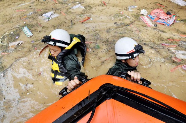 This picture taken on July 15, 2015 shows rescuers pulling a boat through floodwaters after heavy rainfall hit the area in Songtao county in Tongren, in southwest China's Guizhou province. (Photo by AFP Photo/Stringer)