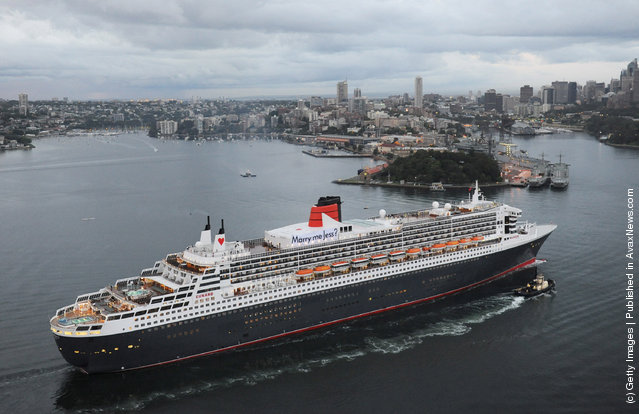A banner with the message 'Marry Me Jess?' hangs from the funnel of the Queen Mary 2 as it arrives into Sydney Harbour on Valentines day, February 14, 2012 in Sydney, Australia