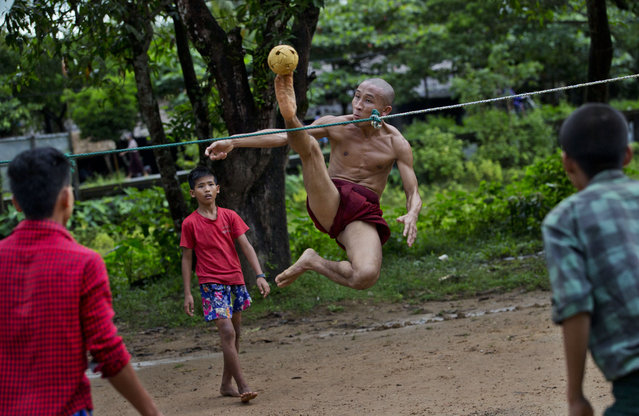 In this Sunday, Sept. 29, 2013 photo, an airborne Buddhist monk kicks a rattan ball during a game of Chinlone in Kawhmu, Myanmar, southwest of Yangon. A combination of sport and dance, it is played between two teams of six players each, passing the ball back and forth with their feet, knees or heads. (Photo by Gemunu Amarasinghe/AP Photo)
