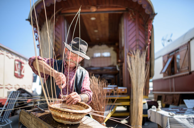 """A gypsy weaves a cup in front of his wagon with a painting of """"Sara the Black"""" on May 24, 2016 in Staintes Maries de la Mere near Arles, France. (Photo by Thomas Lohnes/Getty Images)"""