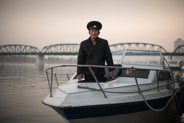 In this photo taken on November 25, 2016, sailor Kim Il-Su (Kim Il-Soo) poses for a photo on a boat used to host wedding photo shoots on the Taedong river in Pyongyang. (Photo by Ed Jones/AFP Photo)