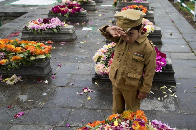 A Kashmiri Muslim boy dressed in a police uniform salutes after offering flowers at the Martyr's Graveyard in Srinagar, Indian controlled Kashmir, Monday, July 13, 2015. Parts of Indian-controlled Kashmir remained under curfew to stop a rally by separatist groups in memory of the day in 1931 when the region's Hindu king ordered more than 20 Kashmiri Muslims executed in a bid to put down an uprising. July 13 is observed as Martyrs' Day in the state. (Photo by Dar Yasin/AP Photo)