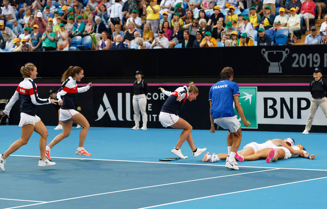 France's Caroline Garcia, right, and Kristina Mladenovic lie on the court as they are swamped by teammates after winning their doubles match against Australia to win the Fed Cup tennis final in Perth, Australia, Sunday, November 10, 2019. (Photo by Trevor Collens/AP Photo)