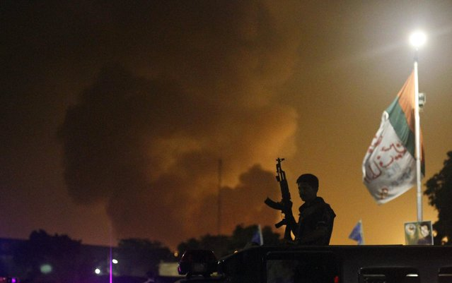 A policeman with a gun stands on a vehicle as smoke billows from Jinnah International airport in Karachi, June 9, 2014. REUTERS/Athar Hussain