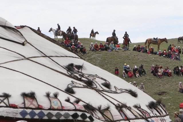 People gather before the Kyrgyz national horse games and festival near the Tulpar-Kul lake in the Chon Alai mountain range, some 3500 metres (11483 feet) above sea level, in the Osh region of Kyrgyzstan, July 25, 2015. (Photo by Vladimir Pirogov/Reuters)