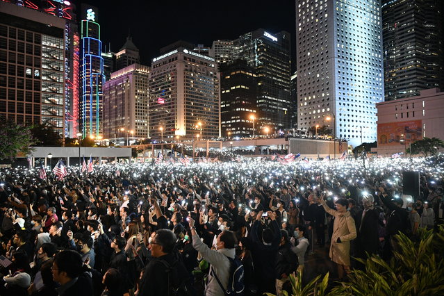 People hold up lights from their mobile phones as they take part in a gathering of thanks at Edinburgh Place in Hong Kong's Central district on November 28, 2019, after US President Donald Trump signed legislation requiring an annual review of freedoms in Hong Kong. China on November 28 threatened to retaliate after US President Donald Trump signed legislation supporting Hong Kong pro-democracy protesters, just as the world's top two economies edge towards a trade truce. (Photo by Anthony Wallace/AFP Photo)