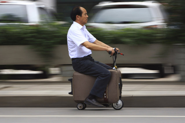 He Liang rides his home-made suitcase vehicle along a street in Changsha, Hunan province May 28, 2014. He spent 10 years modifying the suitcase into a motor-driven vehicle. The suitcase has a top speed of up to 20km/h and the power capacity to travel up to 50-60km after one charge, according to local media. (Photo by Reuters/China Daily)