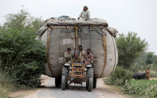 Farmers ride home on a tractor pulling an overloaded trailer full of straw in a village outside Faisalabad, Pakistan May 3, 2017. (Photo by Caren Firouz/Reuters)