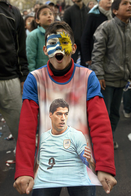A soccer fan, with his face painted to represent his country's flag and wearing a T-shirt with an image of Uruguayan footballer Luis Suarez, cheers as he watches a live broadcast of the World Cup match between England and Uruguay in downtown Montevideo, Uruguay, Thursday, June 19, 2014. (Photo by Matilde Campodonico/AP Photo)
