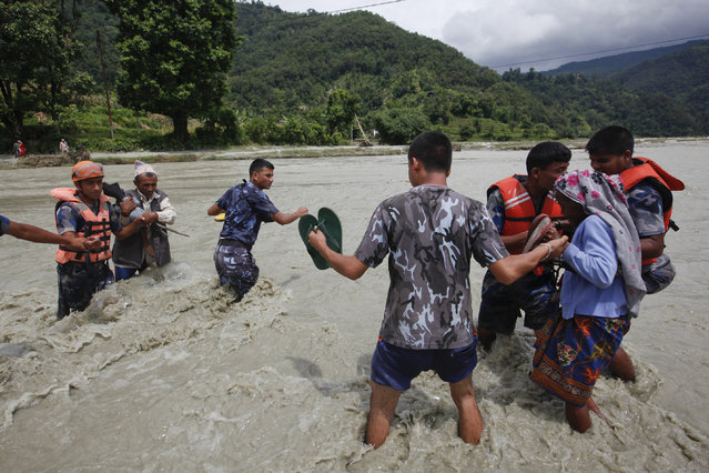 Nepalese rescue team helps local people cross a river after a foot bridge was destroyed by floods in Thulakhet, about 200 kilometers (125 miles) west of Kathmandu, Nepal, Friday, July 31, 2015. (Photo by Niranjan Shrestha/AP Photo)