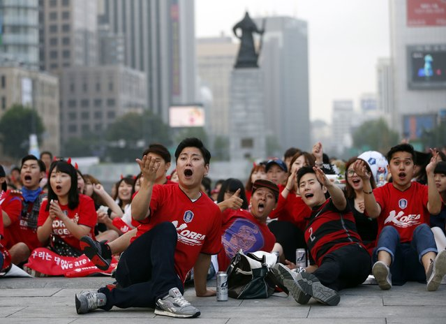 Soccer fans of South Korea react as they watch a live television broadcast of their 2014 World Cup Group H soccer match against Belgium, in Seoul June 27, 2014. Jan Vertonghen's late goal saw 10-man Belgium beat South Korea 1-0 in their final Group H match on Thursday, despite having Steven Defour sent off just before halftime for a nasty two-footed challenge. (Photo by Kim Hong-Ji/Reuters)