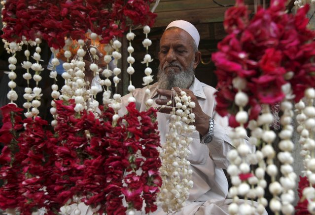 A man weaves jasmine flowers and roses to make garlands at a stall in Karachi, Pakistan, July 28, 2015. (Photo by Athar Hussain/Reuters)