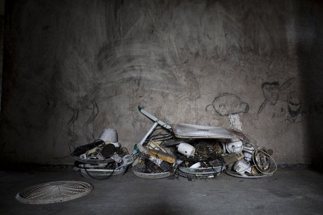 In this June 29, 2015 photo, fan parts recovered by Jimmy Bellefleur sit stacked in the hallway of the abandoned, earthquake damaged government office building where he lives with his family in Port-au-Prince, Haiti. Bellefleur's work as an electrician enables him to buy food and afford relative luxuries such as a double bed and the used televisions and fans he's brought back to life. (Photo by Rebecca Blackwell/AP Photo)