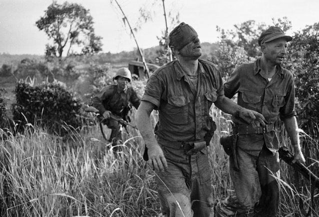 In this August 19, 1965, file photo, made by Peter Arnett, a U.S. Marine who was wounded in the head as he fought against the Viet Cong from inside an amphibious tank, is led to an evacuation helicopter landing zone at Van Tuong, Vietnam. (Photo by Peter Arnett/AP Photo)
